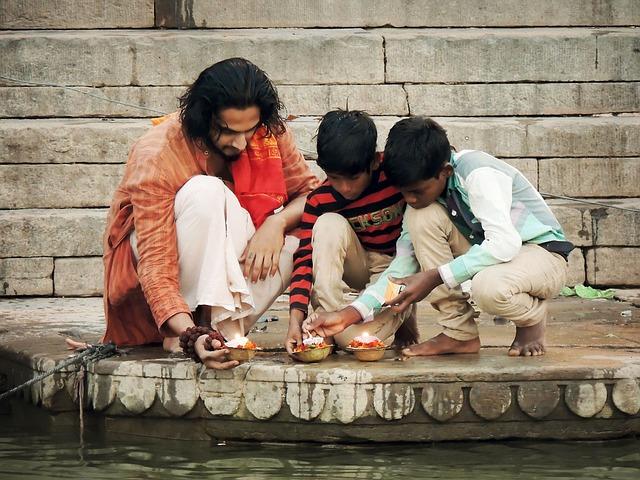 Spirituelle Inder mit Kerzen am Wasser